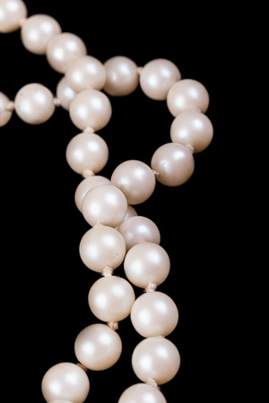 a necklace made of beautiful pearls on a black velvet cloth photo