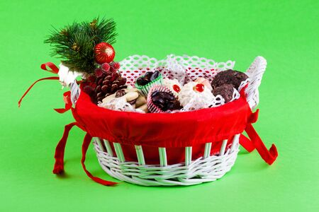a festive christmas basket filled with cookies and candy over a green background photo