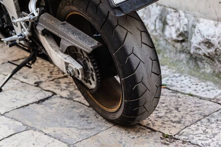 the rear wheel of a powerful motorcycle on the street photo