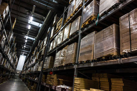 a dark and big warehouse with a lot of boxes on the shelves