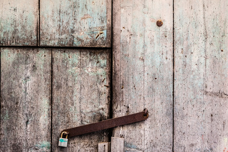 a rusty and weathered old door closed with a padlock photo