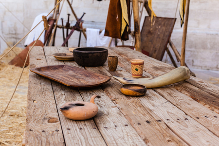 a big and old wooden table with some medieval items on it