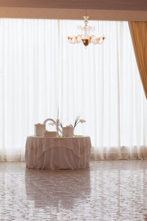 a white table with wedding favors in a big luxurious hall Stock Photo - 27260124