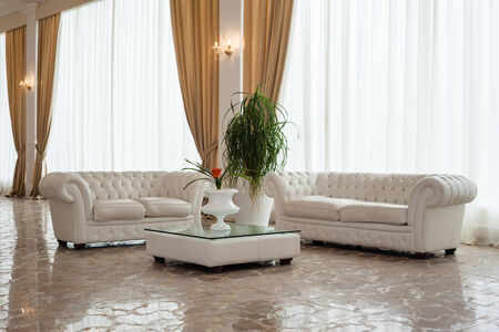 a luxurious and big modern living room with white furnitures