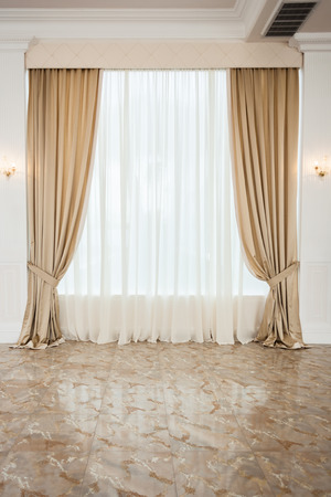 luxury beige drapes in a big luminous hall Foto de archivo
