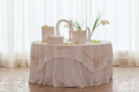 a white table with wedding favors in a big luxurious hall Stock Photo - 27260186