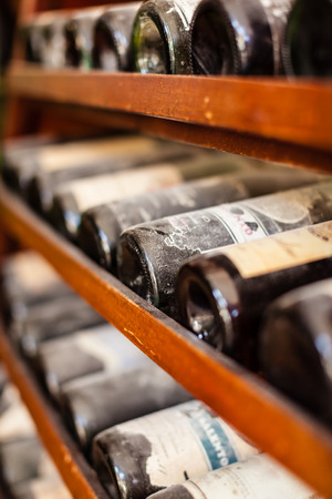 a lot of very old dusty wine bottles in an italian cellar