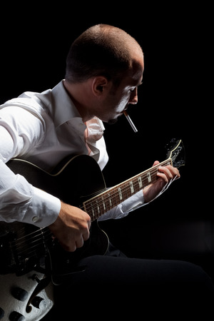 hand jamming: a young jazzer with a black acoustig guitar over black background