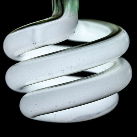macro shot of a dirty compact fluorescent bulb over a black background photo
