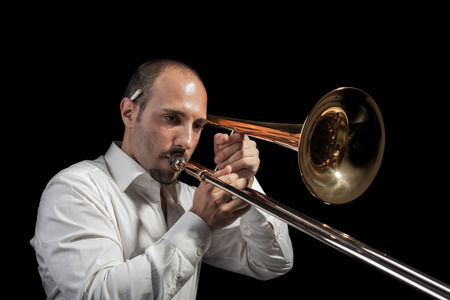 a young jazzer with a trombone over black