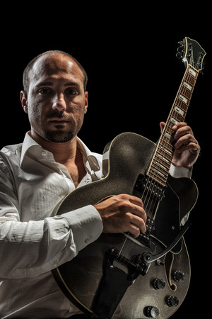 a young jazzer with a black acoustig guitar over black background photo