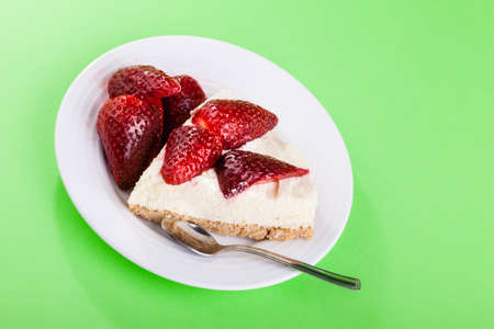a delicious custard cake with strawberries on a white plate on a green background photo