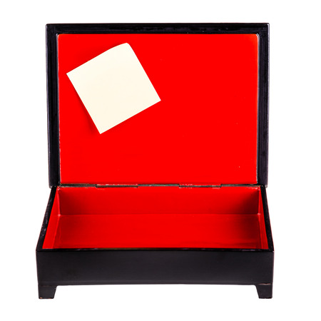 a black laquered box with a bright red interior and a post it isolated over white
