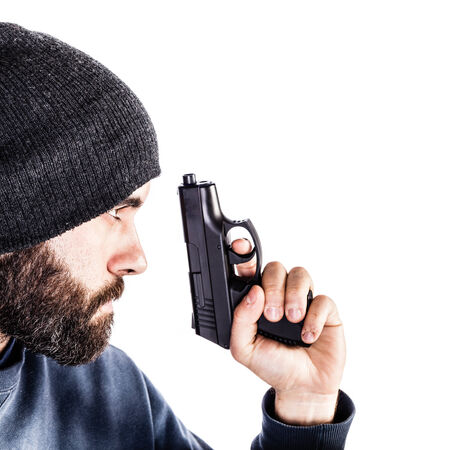 law enforcer: a bearded criminal or an undercover cop with a pistol and wearing a beanie hat isolated over white
