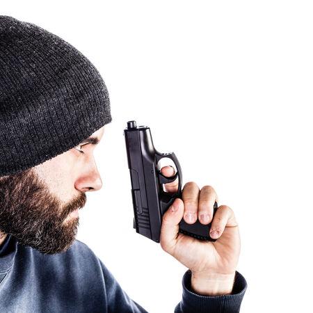 undercover: un criminale con la barba o un poliziotto sotto copertura con una pistola e indossa un cappello beanie isolato su bianco