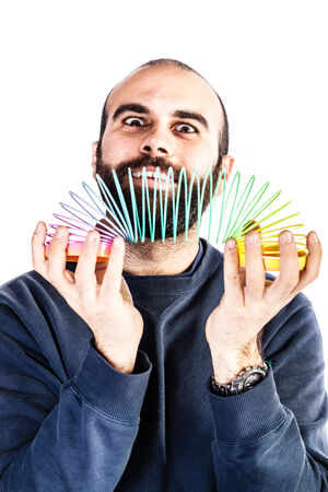 a bearded man playing with a rainbow slinky toy and looking silly photo