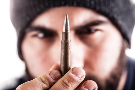 a bearded man wearing a beanie hat holding a sniper bullet and looking at it. Isolated over white