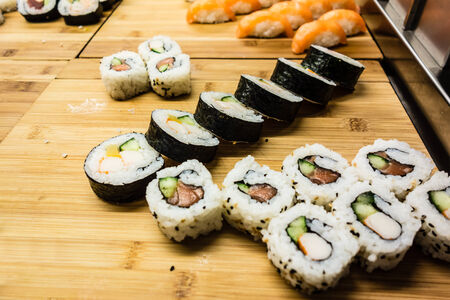 a lot of maki sushi on a wooden board photo