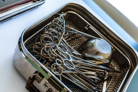 surgical instruments and tools including scalpels, forceps and tweezers in a metal container