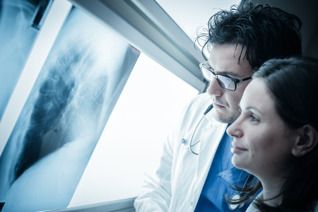 two yound doctors examining a x-ray film at the diaphanoscope Stockfoto