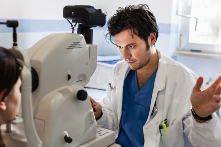 eye doctor: a young ophthalmologist using a non-mydriatic retinal camera on a young girl