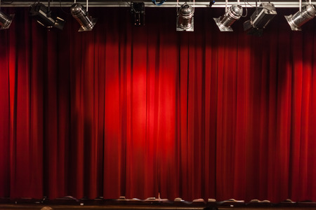 a closed red stage curtain in a small theater Stock Photo