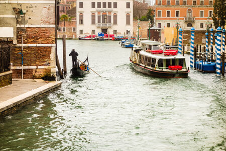Narrow canal among old colorful brick houses in Venice, Italy. photo