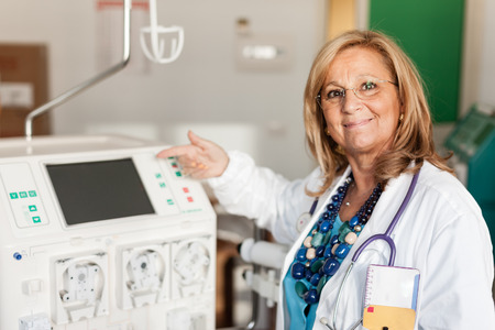 a female doctor showing how to use a dialysis machine