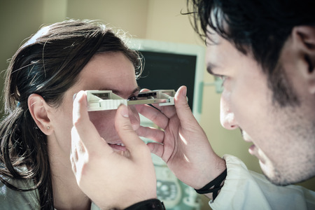displacement: a young ophthalmologist using an exophthalmometer, an instrument used for measuring the degree of forward displacement of the eye in exophthalmos Stock Photo