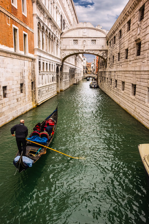 passing over: Gondolas passing over Bridge of Sighs - Ponte dei Sospiri. A legend says that lovers will be granted eternal love if they kiss on a gondola at sunset under the Bridge. Venice,Veneto, Italy, Europe.
