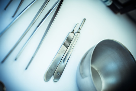 surgery table: surgical instruments and tools including scalpels, forceps and tweezers arranged on a table for a surgery