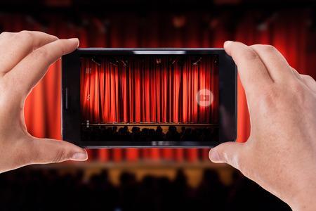 sipario chiuso: un telefono cellulare di scattare una foto in un teatro con la tenda rossa chiusa