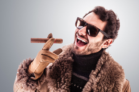 a young and rich man wearing a sheepskin coat isolated over a white background holding a cigar photo