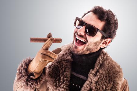 rich man: un hombre joven y rico que llevaba un abrigo de piel de oveja aislada sobre un fondo blanco que sostiene un cigarro
