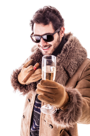 a young man wearing a sheepskin coat isolated over a white background holding a cigar and a glass with champagne
