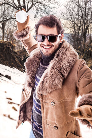 a young man wearing a sheepskin coat  playing with a snowball photo