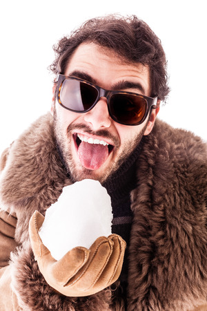 a young man wearing a sheepskin coat isolated over a white background playing with a snowball photo
