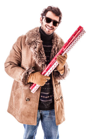 a young man wearing a sheepskin coat and holding wrapping paper for christmas gift. Isolated over white photo