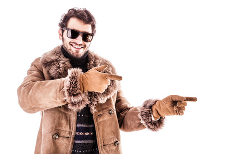 a young man wearing a sheepskin coat isolated over a white background photo