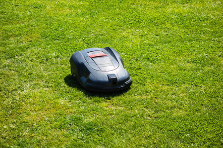 a robotic lawn mower working on a green grass field Stockfoto