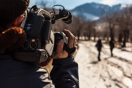 a young man using a professional camcorder outdoor