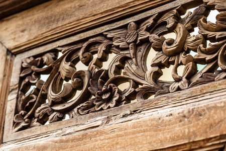 close up shot of some intricate floral patterns carvings on a wood panel photo