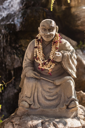 statue of a wise chinese or buddhist mong in a zen garden in the Wat Pho Temple, Thailand photo