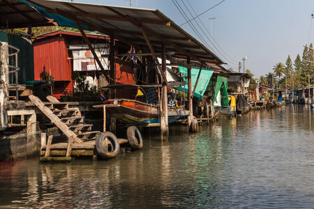 stilted: hovels of a small village on the riverside of a canal in the thai countryside in Ratchaburi district, Thailand Stock Photo
