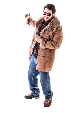 a cheerful young man wearing an expensive sheepskin furry coat isolated over a white presenting something in the back photo
