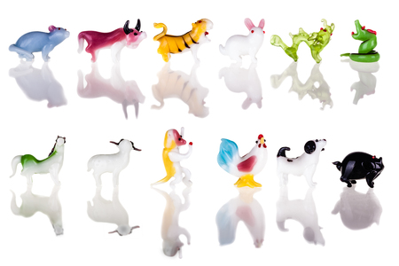 small glass sculptures representing the chinese zodiac signs isolated over a pure white background photo