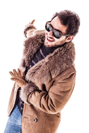 a cheerful young man wearing an expensive sheepskin furry coat isolated over a white background presenting something in the back photo