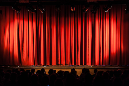 a closed red stage curtain in a small theater 스톡 콘텐츠