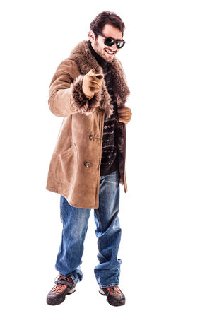 a cheerful young man wearing an expensive sheepskin furry coat isolated over a white background photo