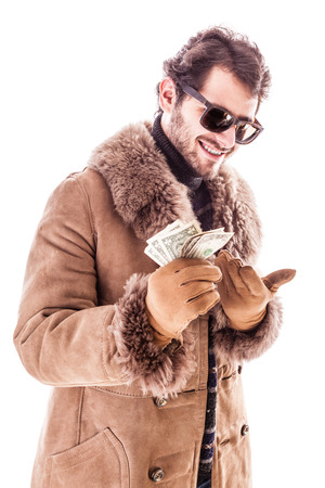 a young man wearing a sheepskin coat isolated over a white background holding banknotes Imagens